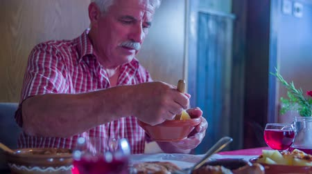 cracknel : An older man is serving himself some potatoes and putting them on his plate. Close-up shot.