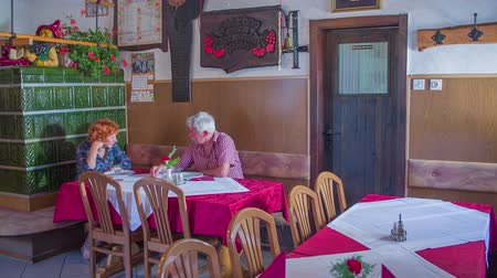 cracknel : An old couple is sitting down at a restaurant table and talking to each other. In the background, we can see a farmhouse stove and the place is very traditionally decorated. Wide-angle shot. Stock Footage