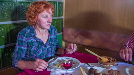 cracknel : A senior woman is enjoying her meal in a restaurant that serves traditional food. Close-up shot of a woman. Stock Footage