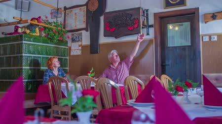 cracknel : An old man and woman are talking with each other in an old-fashioned restaurant. The man also rings a bell in between. The woman is also looking around to see how the place is decorated. Wide-angle shot.