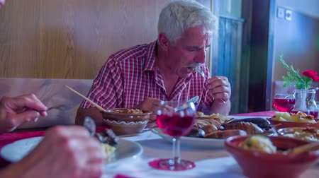 cuisine of different countries : A senior man and his wife are sitting in a restaurant with local food and we can the man how he is enjoying his food. There is a lot of different food on the table. Close-up shot. Stock Footage