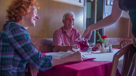 cracknel : A young waitress is bringing some red wine to the table where an old couple is sitting. She is pouring some red wine into their glasses. They are both smiling and talking to her for a bit. Close-up shot.