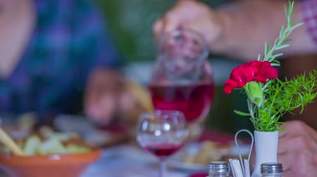 cracknel : Old man is pouring some red wine into glasses for him and his wife. There is a red carnation in a vase on a table. A man and woman are also toasting with their glasses. Close-up shot. Stock Footage