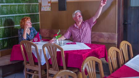 iyi olmak : An older man is ringing the bell in a restaurant. The bell was supposed to be for good luck. Him and his wife are laughing. They are both having a good time. Wide-angle shot.