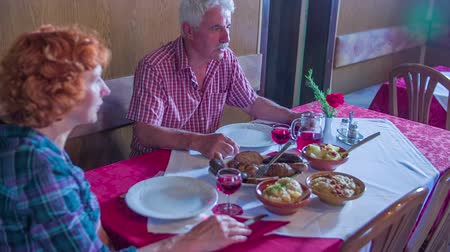 více barevné : A senior couple is sitting at a table when the waitress brings out more food. They are both excited to try the local cuisine. The room is decorated traditionally.