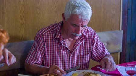 cracknel : A senior man and his wife are enjoying the local cuisine in a restaurant. They are both loving the food that was served for them. Close-up shot of a man eating.