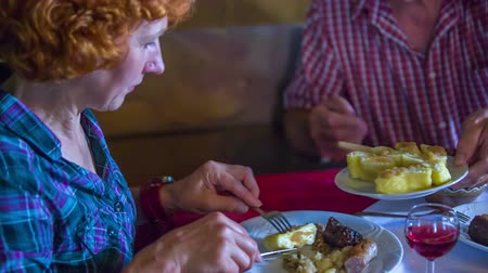 cracknel : Older couple eating cottage cheese rolled dumplings in a traditional restaurant that serves local food. The man is offering the rolled dumplings to is wife. Close-up shot. Stock Footage
