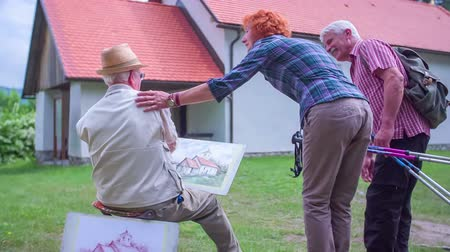 hat : Two older hikers are coming on top of the hill where the artist is creating his drawing of the church. They are saying hi to him, they talk a little and then they wave him goodbye. Wide-angle shot from behind. The artist also lifts his hat up to say hi to Stock mozgókép