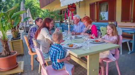 сады : Family is eating lunch outside in a restaurant and talking. They are enjoying their time, the day is beautiful and bright. There are some palm trees outside, too. Стоковые видеозаписи