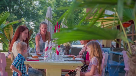 quintal : Waitress is bringing plates with meat on the table in a restaurant where the family is gathered. They are sitting outside and the day is beautiful and sunny. The family is also talking among each other.