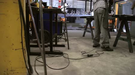 munkás : In this video, we can see a worker welding in the production shop. Wide-angle shot.