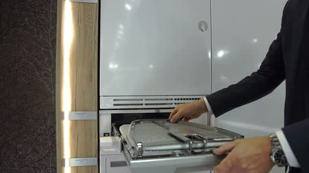 yerleşim : In this video, we can see a businessman unfolding the ironing board by Gorenje Company that is stored on the bottom of the dryer and describing it to the visitors of the fair. Close-up shot. Stok Video