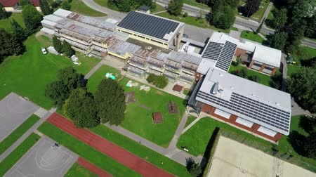 панель : This is air view on school with solar panels and big spacious playground which is on a beautiful location in the middle of nature which is placed in a beautiful environment on countryside.