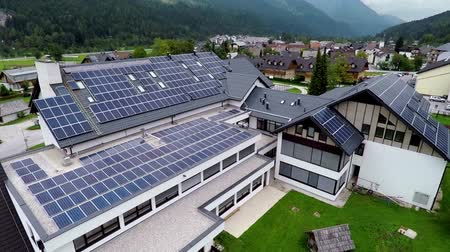 панель : This is air view on school with solar panels on roof which is on a beautiful location in the middle of nature which is placed in a beautiful environment on countryside.