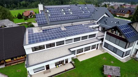 панель : This is air view on school roof which has a lot of solar panels and it is on a beautiful location in the middle of nature which is placed in a beautiful environment on countryside.