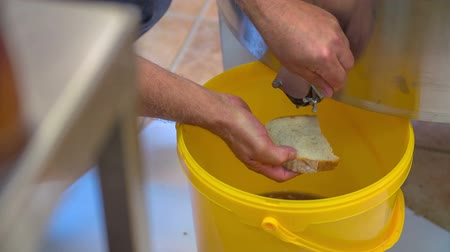 full bucket : The man is putting honey on bread from a barrel in a store where honey is produced