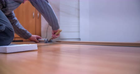 instalação : A man is using a hammer to check if all sides are even. He and his friend are laying wood panels to build a new floor. Close-up shot. Vídeos
