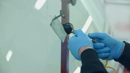 üveges : A man is trying to fix a window crack on a car that was taken to a car repair shop. This device will help solve a problem. Close-up shop.