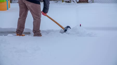 gyalogút : In this video, we can see that a man is shovelling snow and clearing a path. Close-up shot.