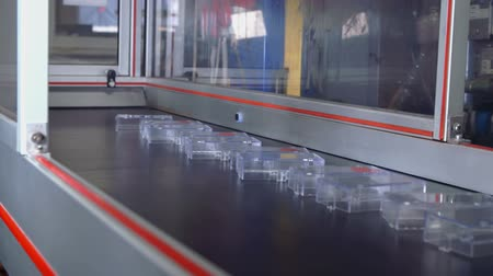 plastic cups : In this video, we can see that a robot is dropping a small plastic item on a conveyor belt and then moving back up. Stock Footage
