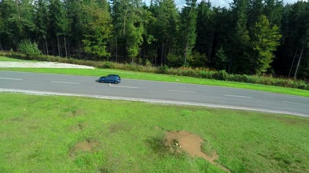 stopy : In this video, we can see that a blue sports car is driving on a track next to the forest. Close-up shot.