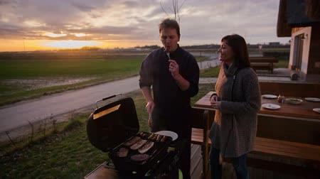 bbq grill : Wife and husband are cooking on a barbecue grill. A man offers his wife a bite of meat, she tries it and she likes it. She kisses her husband on his cheek. The sunset in the background is amazing. Stock Footage