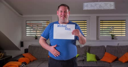 nadváha : A young man shows a piece of paper with the title Work-out Plan. He then taps on his stomach as if to say that he needs to lose weight on this part of the body. He smiles.
