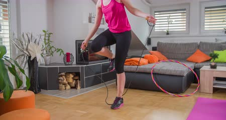 nem sikerül : A lady is jumping rope at home which is a great way to exercise her body. She fails a couple of times but then she continues doing it and she gets better and better. Wide-angle shot.