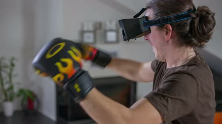 úgy néz ki : A young guy is boxing with in his living room at home with VR glasses on and his boxing gloves. He is doing it very fast and it looks like a great exercise. Stock mozgókép