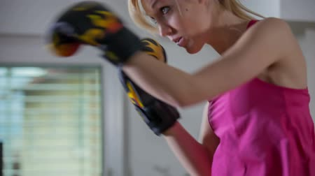 boxe : A woman is having big boxing gloves on and is working out at home in her living room. Close-up shot.