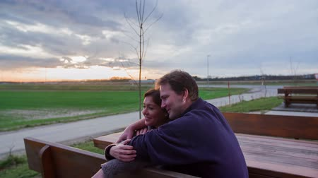 přední : A senior couple is sitting on a bench and are having a lovely time together. They are showing love and devotion to each other. The sunset behind them is fascinating.