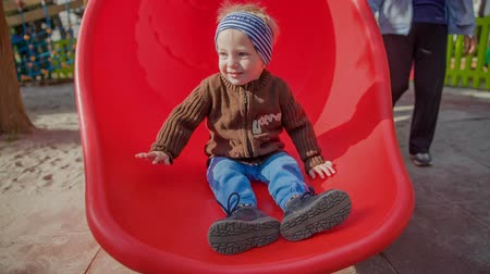 slayt : A small little boy is cheerful and happy when he is coming down a red slide in the playground. His grandma is looking after him.
