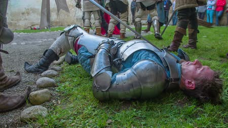 средневековый : A battle is now finished and some knights are lying motionless on the ground, some are injured and some are the winners. Close-up shot.
