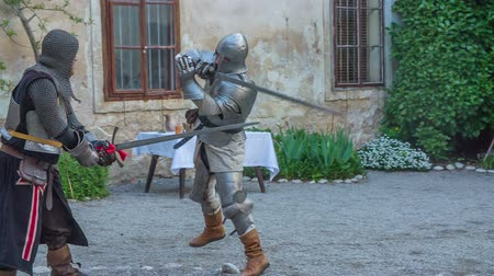 história : Two knights are fencing in the courtyard of a castle. One of them is dressed in an armour. Wide-angle shot.