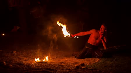 rycerz : A young man is performing a short choreography for the audience and he is spewing fire. It is evening time. Wide-angle shot.