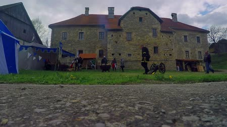 zamek : Knight is walking up to a small tent. There is a castle in the background. Wide-angle shot.