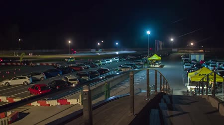 prawo jazdy : We can see a safe driving center during night time and many cars are parked in the parking lot. Wide-angle shot.