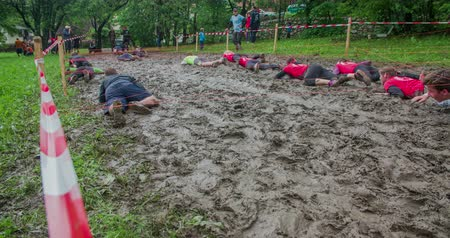 obstacles : EVENT URBANI GLADIATOR CELJE, 2016:  All the teams are crawling very slowly across the mud pool but then two guys are coming and are going to the other side very fast. Wide-angle shot.