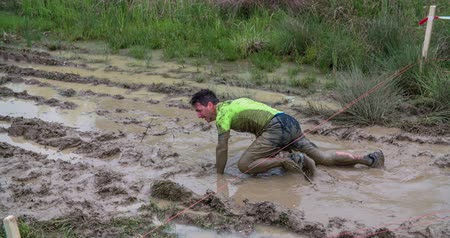 obstacles : EVENT URBANI GLADIATOR CELJE, 2016:  This young guy has successfully completed a mud challenge and he is shaking off the dirt. Wide-angle shot. Stock Footage