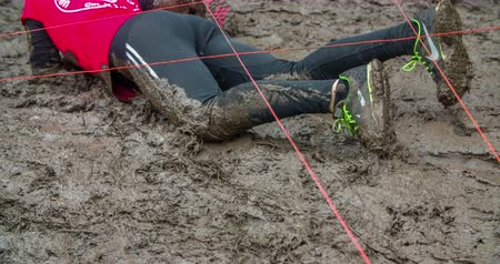 obstacles : EVENT URBANI GLADIATOR CELJE, 2016:  A lady from the red team is slowly moving across the mud pool. The ground is very slippery. Close-up shot.