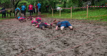 obstacles : EVENT URBANI GLADIATOR CELJE, 2016:  The red team is crawling across the mud pool one after the other. They will soon come to the other side. Wide-angle shot.