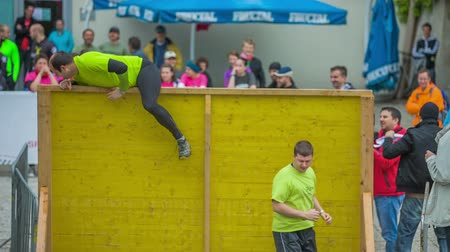 climbed : EVENT URBANI GLADIATOR CELJE 2016 Two competitors have successfully climbed over a yellow hurdle and when they jump down on the other side, they give high five to each other and continue running to the next challenge. Wide-angle shot.