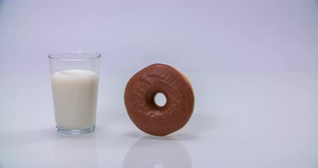 úgy néz ki : A doughnut is rolling on a table and then it stops next to a glass of milk. This looks like a delicious snack. Wide-angle shot.