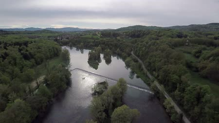 rytíř : There is a river and there are many forests surrounding it. The day looks a bit rainy and not sunny. There are some mountains in the background, too. Wide-angle aerial shot.