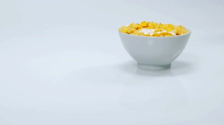 iyi olmak : A cup of corn flakes is standing on the table and someone is pouring some milk into it. This will be a very good and healthy breakfast. Close-up shot. Stok Video