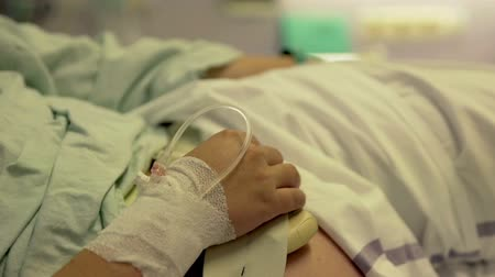 labour ward : A pregnant woman is resting on a hospital bed and she has an injection in her hand. Close-up shot. Stock Footage