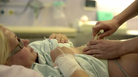 labour ward : A nurse is taking something off which was around the pregnant womans stomach. Close-up shot. Stock Footage