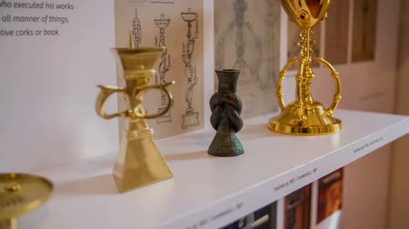 local de nascimento : There are different golden items displayed on a shelf in Plecniks house. Close-up shot.