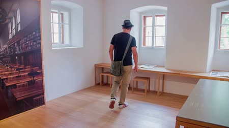 local de nascimento : A young visitor walks into a room which is now a museum and he picks up a brochure and starts reading it. This is Plecnik House. Wide-angle shot.