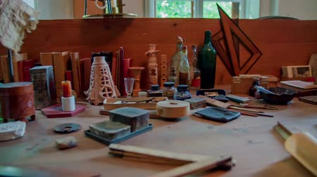 senhor : We can see a room and a table where Mr Ple?nik used to work and create. There are different items and tools on the table. Close-up shot.